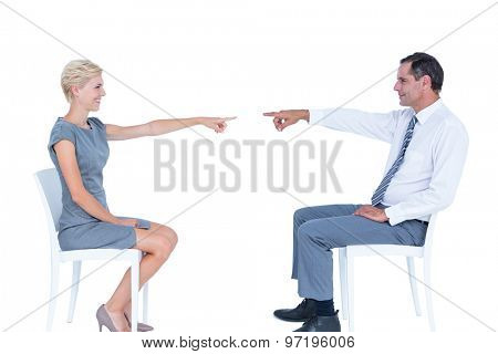 business people pointing at each other against a white wall