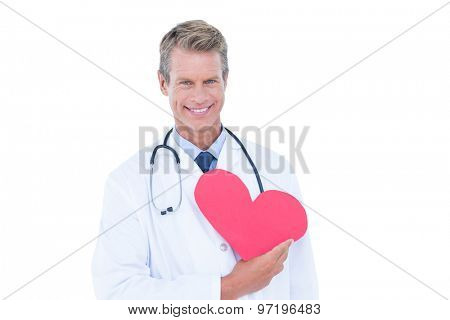 Smiling doctor holding heart card on white background