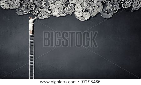 Rear view of businesswoman standing on top of ladder