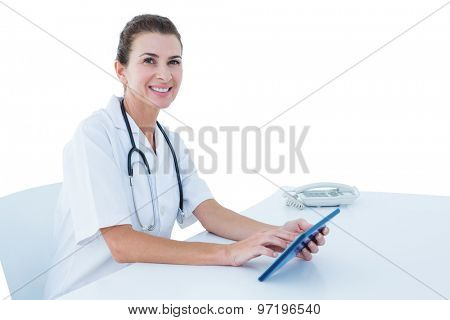 Young doctor standing with tablet pc against white wall