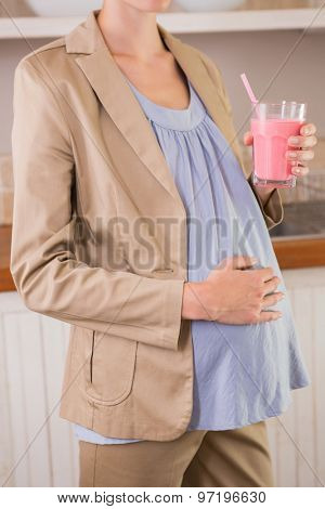 Blonde pergnancy drinking a smoothie in the kitchen