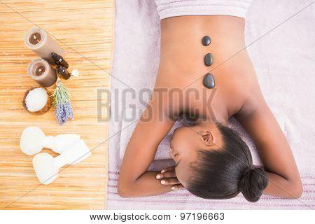 Pretty woman enjoying a hot stone massage at the health spa