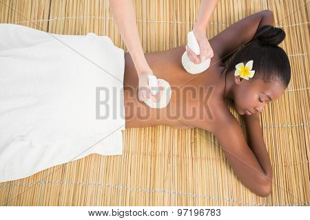 Upward view of a pretty woman enjoying a herbal compress massage