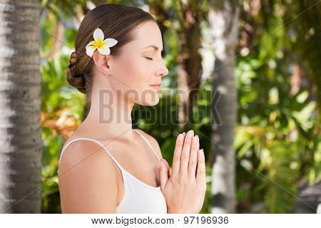 Beautiful natural brunette doing yoga on green background