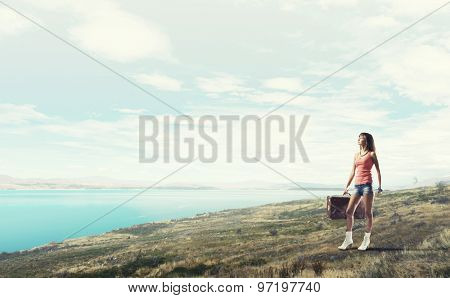 Traveler woman walking with retro suitcase in hand