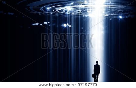 Rear view of businessman standing in light of way