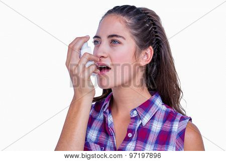 Pretty brunette woman using asthma inhaler on white background