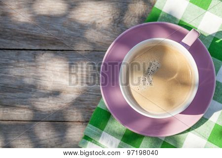 Coffee cup on garden table. Top view with copy space