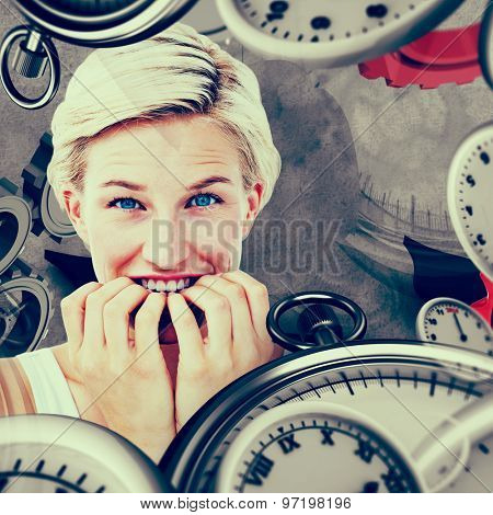 Nervous woman biting her nails looking at camera against grey background