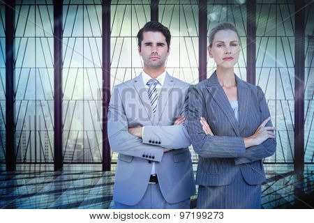 Business people with arms crossed looking at camera against window overlooking city