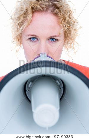 Pretty blonde speaking into megaphone on white background