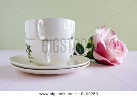 China Teacups And A Single Pink Rose Flower