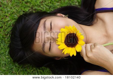 Asian lady smelling flower on grass