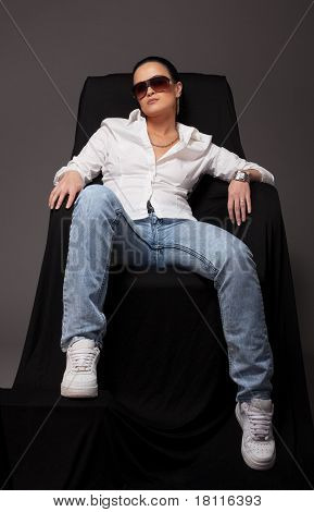 Young girl like tomboy sit on black chair