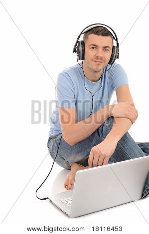 Young Handsome Man Listening To Music In Headphones From Computer. Isolated