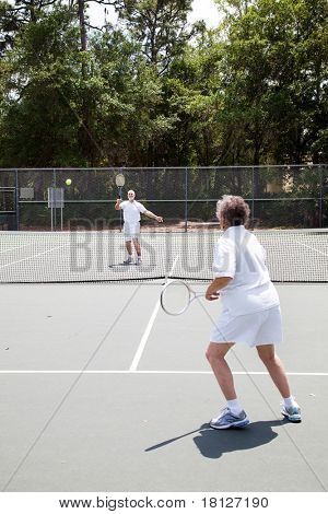 Senior man and woman playing in a tennis match.