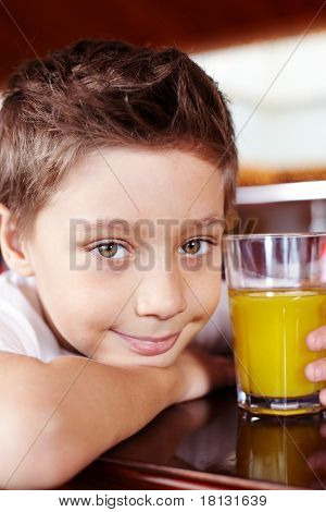 Portrait of cute lad with glass of juice looking at camera in cafe