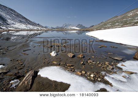 Stones and snow near mountain lake. The pass Baikonur, Eastern Sayan mountains. Siberia.