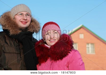 Mann und Frau Lächeln im Winter im freien, Haus, rote Ziegel, blauer Himmel