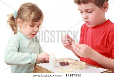 little girl and boy in red T-shirt crafts at small table, keenness