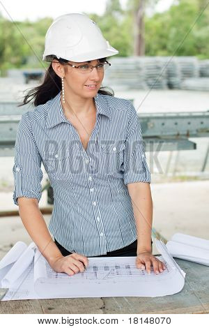 Smiling Young Engineer Woman Read Drawings And Looks Aside