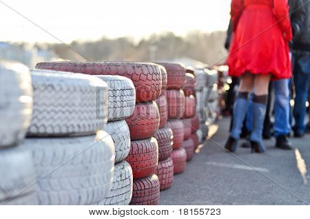 racetrack fence of white and red of old tires and female legs in boots