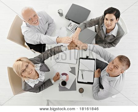 Businessteam raising hands together at meeting, expressing teamwork, sitting at table, smiling, overhead view.?