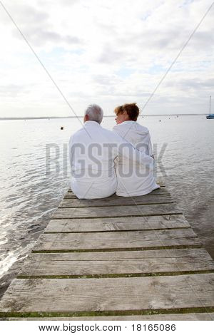 Senior couple in bathrobe sitting on a pontoon