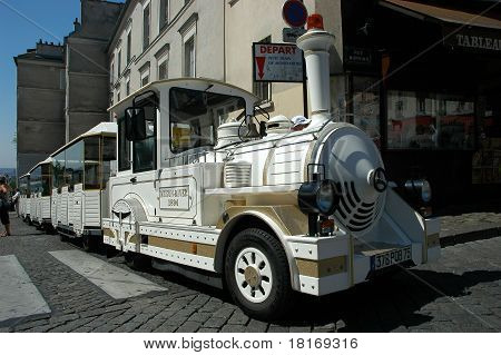 Small train for tourists stops in front of souvenir stores in Montmarte, Paris