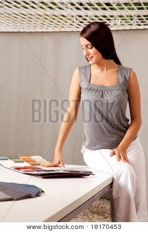 A female interior designer looking at rug samples from a catalog