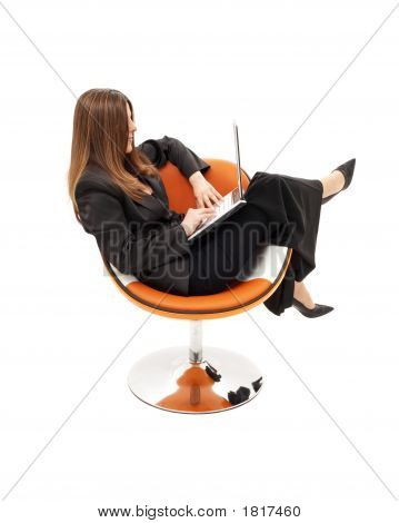 Elegant Businesswoman With Laptop In Orange Chair