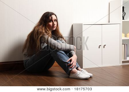 Nervous Frightened Young Girl Sits Alone On Floor