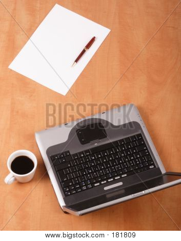 Blank Paper,pen Cup Of Coffee And Laptop On The Desk