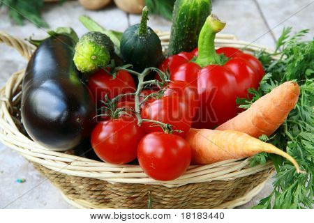 Different fresh vegetables in a wicker basket on the table