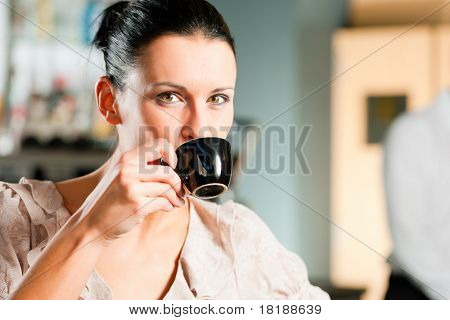 Barista prepares cappuccino in his coffee shop; close-up