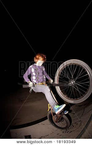 young boy jumpy with his scooter jumping by night