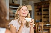 Mature woman holding coffee cup and looking away at cafeteria. Thoughtful mature woman thinking whil poster