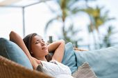 Home lifestyle woman relaxing sleeping on sofa on outdoor patio living room. Happy lady lying down o poster