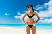 Sport beach woman ready for the summer season. Bikini fitness woman with sun protection hat and sung poster