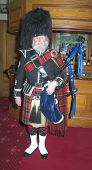 picture of bagpiper  - A Scottish bagpiper in full highland kilt dress and beard holding bagpipes - JPG