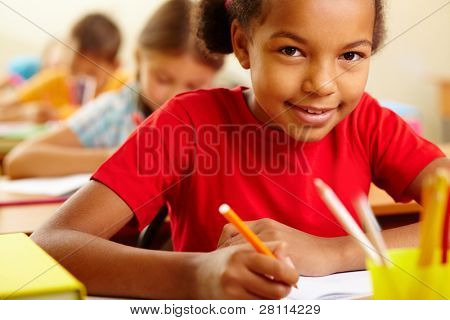 Portrait of lovely girl drawing with crayons and looking at camera