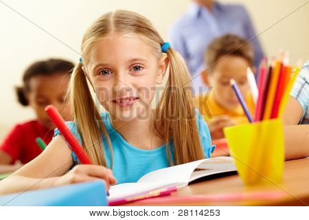 Portrait of lovely schoolgirl looking at camera at lesson
