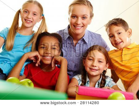 Portrait of smart schoolchildren and their teacher looking at camera in classroom