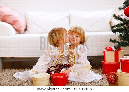 Twin Girl Kissing Her Sister Near Christmas Tree With Gifts