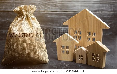 poster of Money Bag With The Word Investments And Wooden Houses. The Concept Of Attracting Investment In Real