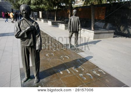 NANJING, CHINA - NOVEMBER 24: Visitors view the statues of the massacre survivors and their recent footprints at the memorial walkway at the Nanjing Massacre Hall on Nov 24, 2011 in Nanjing, China.