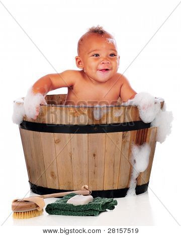 An adorable biracial baby happily taking a bath in an old wooden tub.  On a white background.