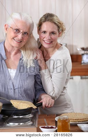 Mother and daughter cooking crepes together