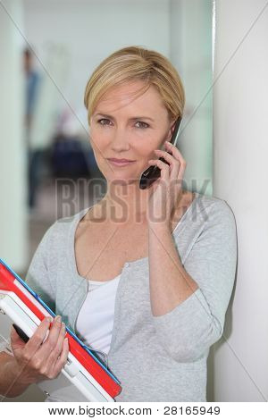 Casually dressed office worker with a pile of paperwork talking on a cellphone