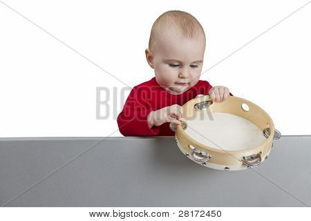 Young Child Holding Tambourine Behind Grey Shield